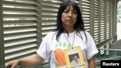 Luz Elena Galeano poses during a interview in Medellin, Colombia, July 15, 2015. Galeano has been searching for her husband (whose photo is hung around her neck) since 2008.