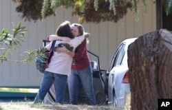 Two women embrace outside Rancho Tehama Elementary School, where a gunman opened fire Tuesday, Nov. 14, 2017, in Corning, Calif.