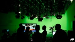 "FILE - employees of the ""Russia Today"" television channel prepare for a visit by Russian President Vladimir Putin to Russia Today's new headquarters in Moscow, Russia."