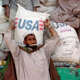 An Afghan man helps unload a shipment of US aid (file photo)
