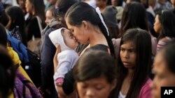 22일 태풍 '하이옌' 생존자가 타클로반 공항에서 구조기탑승을 기다리며 자신의 아기에게 입맞추고 있다.