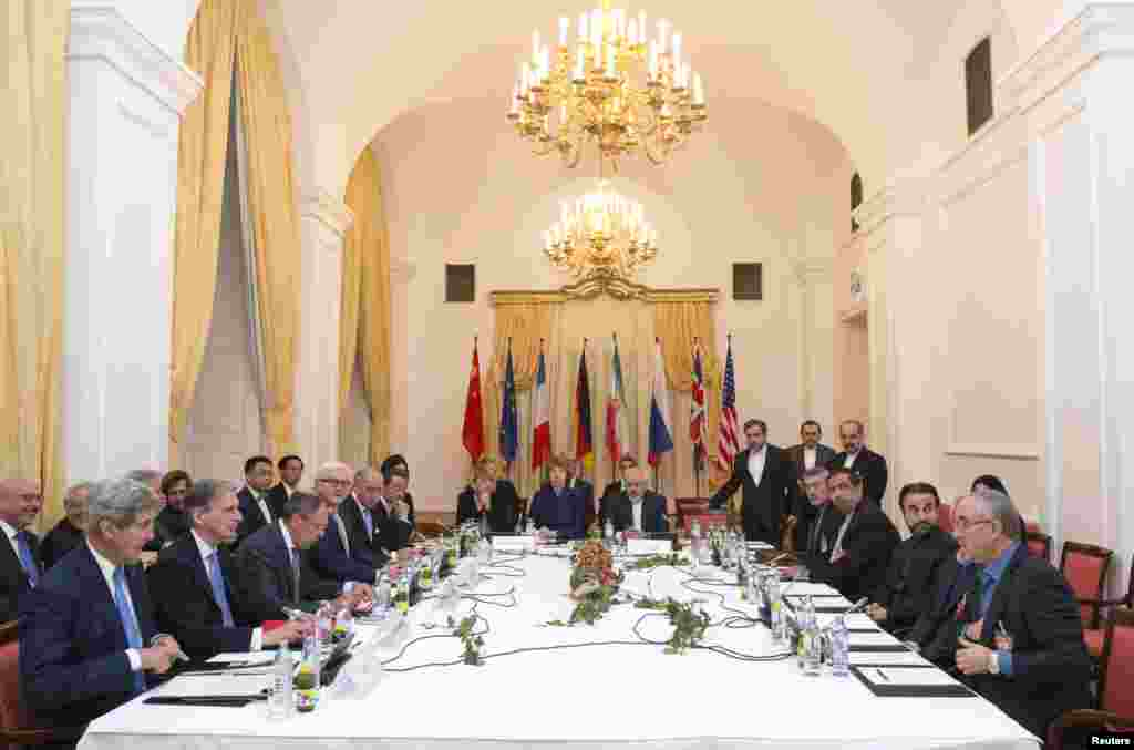 Delegations of U.S. Secretary of State John Kerry, Britain's Foreign Secretary Philip Hammond, Russian Foreign Minister Sergei Lavrov, German Foreign Minister Frank-Walter Steinmeier, French Foreign Minister Laurent Fabius, Chinese Foreign Minister Wang Yi, EU High Representative Catherine Ashton, and Iranian Foreign Minister Javad Zarif sit around the negotiations table during their meeting in Vienna, Nov. 24, 2014.