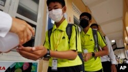 FILE - Students sanitize hands to avoid the contact of coronavirus before their morning class at a high school in Phnom Penh, Cambodia, Tuesday, Jan. 28, 2020.