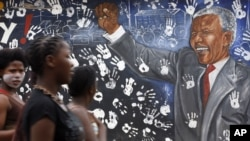 Young women walk pass a mural depicting former South African President Nelson Mandela at Alexandra township in Johannesburg, December 11, 2012.