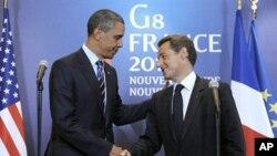 ປະທານາທິບໍດີຝຣັ່ງທ່ານ Nicolas Sarkozy (ຂວາ) ຈັບມືກັບປະທານາທິບໍດີສະຫະລັດທ່ານບາຣັກໂອບາມາ ລຸນຫຼັງການຖະແຫຼງຂ່າວຮ່ວມກັນຫຼັງຈາກການພົບປະ ຢູ່ຂ້າງນອກກອງປະຊຸມສຸດຍອດກຸ່ມຈີ 8 ທີ່ເມືອງ Deauville (27 ພຶດສະພາ 2011)