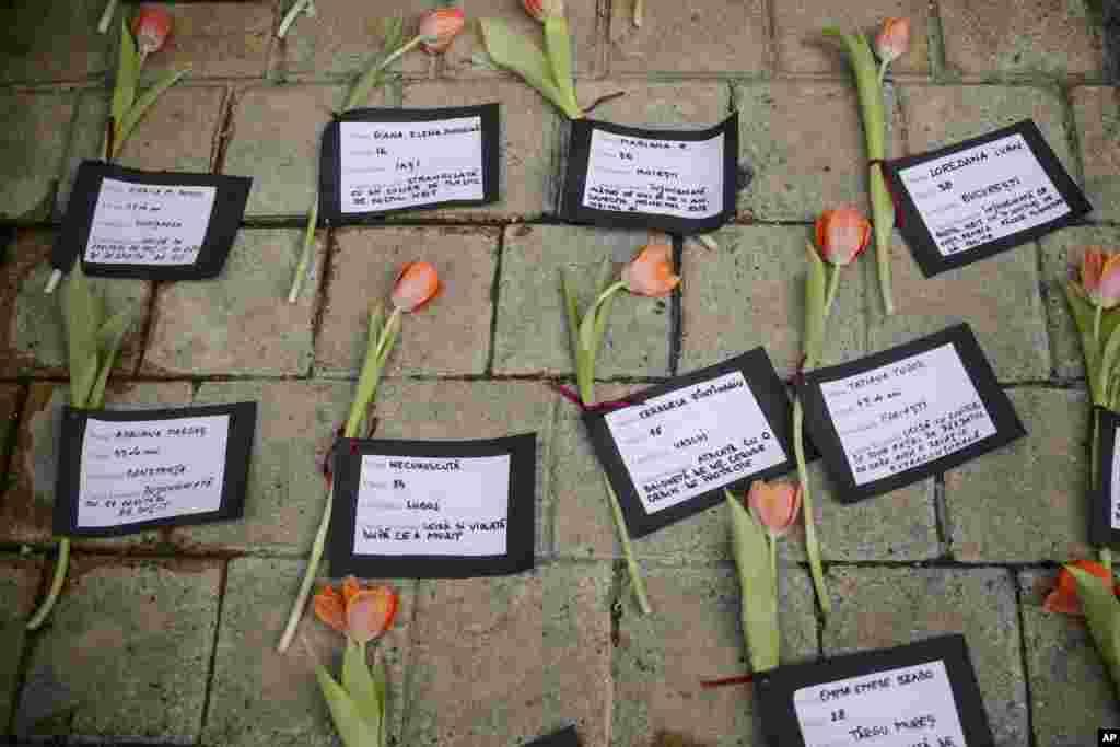 Flowers and cards with names and causes of death are placed on the ground during a performance to raise awareness for the plight of women killed by their partners, in Romania, marking International Women's Day, in Bucharest.