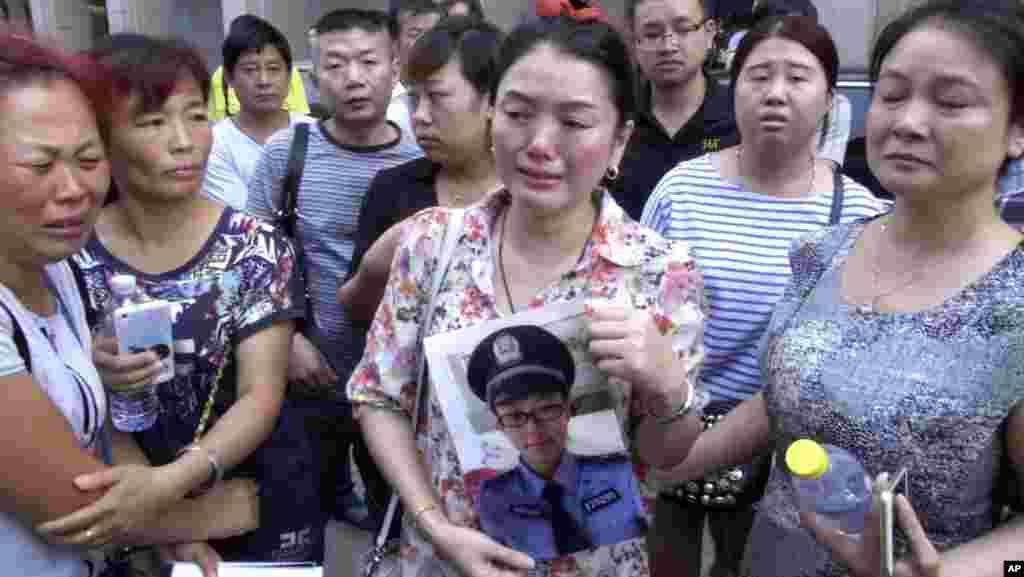 Ảnh chụp từđoạnvideo của AP cho thấy một phụ nữ cầm hìnhcủa con trai là nhân viên cứu hỏa bị mất tích bên ngoài một khách sạn nơi các quan chức tổ chức họp báo tại Thiên Tân, ngày 16/8/2015. Trong số thương vong có nhóm đầu tiên gồm hơn 30 nhân viên cứu hỏa, một chục người đã ùa vội vào để dập tắt một đám cháy. Nhiều người nay đã chết hay mất tích.