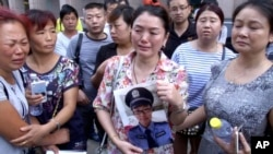 FILE - In this image taken from a video footage from AP Video, a woman holds up a photo of her son, a missing firefighter, outside a hotel where officials held a daily media conferences in northeastern China's Tianjin municipality, Aug. 16, 2015.