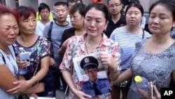Ảnh chụp từ đoạn video của AP cho thấy một phụ nữ cầm hình của con trai là nhân viên cứu hỏa bị mất tích bên ngoài một khách sạn nơi các quan chức tổ chức họp báo tại Thiên Tân, ngày 16/8/2015. Trong số thương vong có nhóm đầu tiên gồm hơn 30 nhân viên cứu hỏa, một chục người đã ùa vội vào để dập tắt đám cháy. Nhiều người nay đã chết hay mất tích.