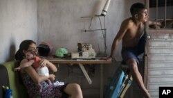 En esta foto de archivo del 23 de diciembre de 2015, Angélica Pereira, tiene a su hija Luiza, nacida con microcefalia por el virus Zika, mientras se sienta con su esposo Dejailson Arruda en su casa de Santa Cruz do Capibaribe , Estado de Pernambuco, Brasil.