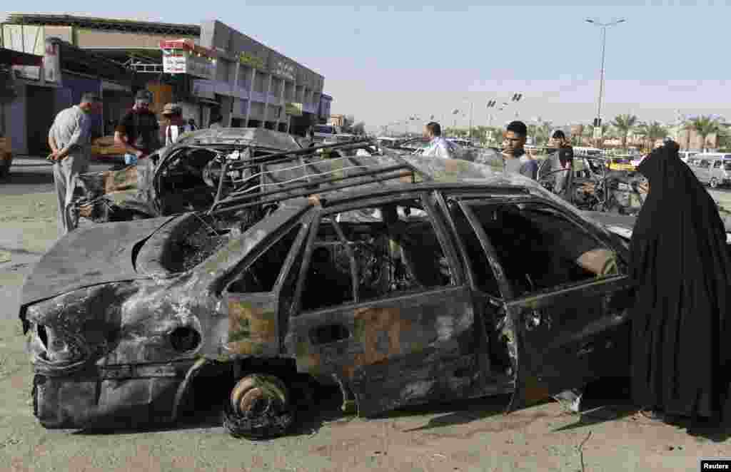 A woman inspects a burnt car at the site of a car bomb attack in Hurriya neighborhood in Baghdad July 3, 2013.