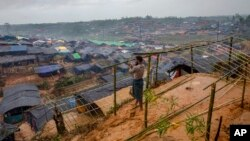 FILE - A Rohingya Muslim man, who crossed over from Myanmar into Bangladesh, builds a shelter for his family in Taiy Khali refugee camp, Bangladesh, Sept. 20, 2017. More than 500,000 Rohingyas poured across the border in late August to escape attacks in Myanmar.