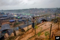 FILE - A Rohingya Muslim man, who crossed over from Myanmar into Bangladesh, builds a shelter for his family in Taiy Khali refugee camp, Bangladesh, Sept. 20, 2017.