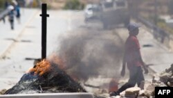 A man walks past burning barricades during a farm workers strike in De Doorns, South Africa, November 14, 2012.
