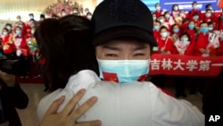 Seorang pekerja medis dari Provinsi Jilin di China bersiap kembali ke daerahnya dari Bandara Wuhan Tianhe di Wuhan, Provinsi Hubei, beberapa jam setelah lockdown 11 minggu karena wabah virus corona dicabut, Rabu, 8 April 2020.(Foto: Reuters)