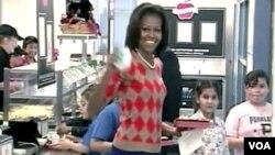 Ibu Negara Michelle Obama makan siang dengan para siswa SD Parklawn di luar kota Washington, DC dalam rangka mengumumkan standar baru makanan sekolah dari Departemen Pertanian yang memperbanyak porsi buah dan sayuran, mengurangi lemak dan garam, lebih ban