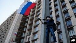 Un manifestante prorruso ondea una mandera rusa en frente de un edificio administrativo en Donetsk, Ucrania, exigiendo anexión a Rusia.