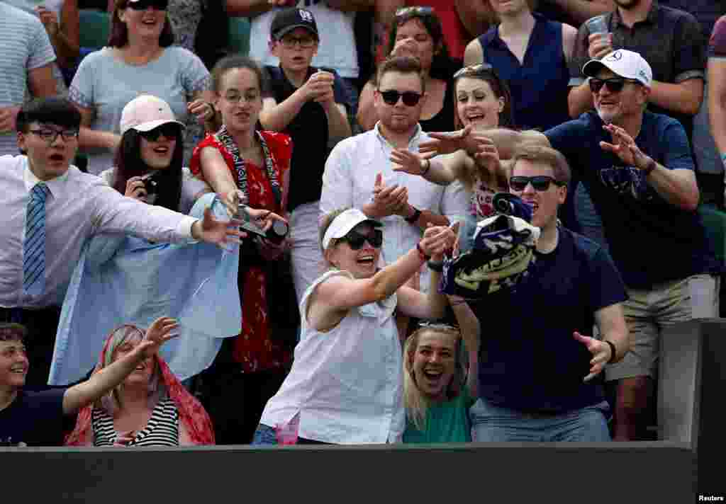Spectators react as Italy's Thomas Fabbiano threw his towel into the stands after winning the second round match against Switzerland's Stan Wawrinka  during the Wimbledon Tennis Championships in London.