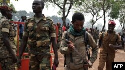 A member of the Central African Armed Forces (FACA) puts his knife away after taking part in the lynching of a man suspected of being a former Seleka rebel on Feb. 5, 2014, in Bangui.