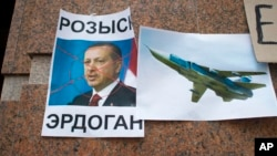 "A poster displaying a portrait of Turkish President Recep Tayyip Erdogan and reading ""Wanted,"" is left after a protest at the Turkish Embassy in Moscow, Nov. 25, 2015, following Turkey's downing of a Russian warplane."