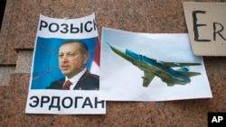 "FILE - A poster showing a portrait of Turkish President Recep Tayyip Erdogan and reading ""Wanted"" is left after a rally protesting the downing by Ankara of a Russian jet, at the Turkish Embassy in Moscow, Nov. 25, 2015."