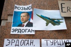 """FILE - Posters showing a portrait of Turkish President Recep Tayyip Erdogan and reading """"Wanted, Erdogan, Turkey,"""" are left after a protest against Ankara's downing of a Russain warplane, at the Turkish Embassy in Moscow, Nov. 25, 2015. Bilateral relations fell to a low point following the incident but have been gradually improving."""