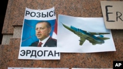 "FILE - Posters showing a portrait of Turkish President Recep Tayyip Erdogan and reading ""Wanted,"" ""Erdogan, Turkey,"" are left after a protest at the Turkish Embassy in Moscow, Nov. 25, 2015. Days earlier Turkey had shot down a Russian fighter jet."