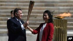 Hellenic Olympic Committee President Spyros Capralos, left, gives the Olympic torch to the former Japanese swimmer Imoto Naoko during the Olympic flame handover ceremony for the 2020 Tokyo Summer Olympics, in Athens, Thursday, March 19, 2020.