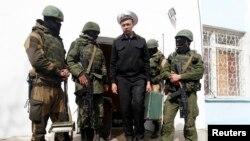 Một sĩ quan hải quân Ukraina (giữa) rời khỏi căn cứ hải quân ở ở Sevastopol được canh gác bởi lính Nga, ngày 19/3/2014.