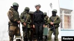 Seorang pejabat angkatan laut Ukraina (tengah) melewati beberapa pria berseragam dan bersenjata, yang diyakini merupakan tentara Rusia, di Sevastopol (19/3). (Reuters/Vasily Fedosenko)