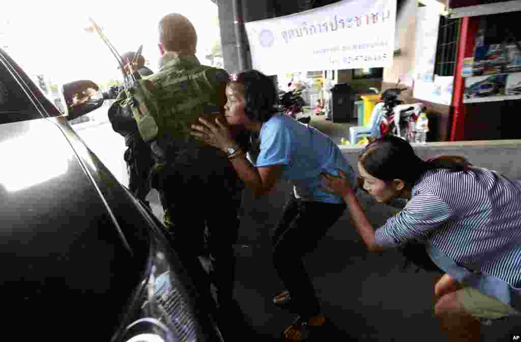 Residents take cover behind Thai soldiers who were sent in to rescue people following clashes between anti- and pro-government groups at a major intersection in Bangkok, Thailand, on the eve of nationwide snap elections. At least seven people are reported wounded, including an American photojournalist.