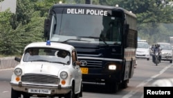 A police bus carries the four men who were found guilty of the rape and death of a 23 year old woman.
