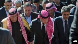 Jordanian King Abdullah II (C), escorted by Safi al-Kaseasbeh (L), father of slain Jordanian pilot, Lt. Muath al-Kaseasbeh, and the pilot's uncle Fahed al-Kaseasbeh, arrive at a memorial tent at their home village of Ai, Jordan, Feb. 5, 2015.