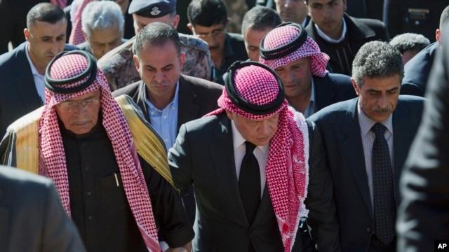 Quốc vương Abdullah II của Jordan (giữa) đi cùng với ông Safi al-Kaseasbeh (trái) thân phụ của viên phi công bị sát hại đến khu trại được dựng lên để tưởng niệm ông, 5/2/15