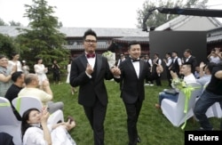 FILE - Gino, left, and Ling Jueding leave after their wedding at a park in Beijing, June 27, 2015. The gay couple had to change the venue for their ceremony nearly 10 times because of intervention from local police. Same-sex marriage is illegal in China, but holding the wedding to mark their 2½-year relationship was a personal wish for the couple, according to Gino.