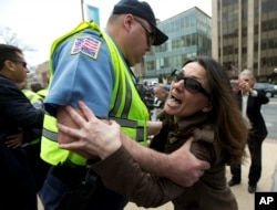 Anti-Erdogan protestor Deniz Lohja, an American of Turkish descent, is prevented by a Washington police officer from crossing near the supporters of Turkish President Recep Tayyip Erdogan, during a rally outside the Brookings Institution in Washington, March 31, 2016.
