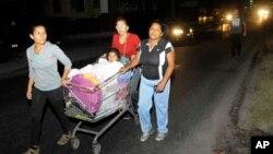 Tiga perempuan mendorong seorang anak yang dalam kereta belanja saat melakukan evakuasi menyusul gempa kuat di Iquique, Chile, Kamis dini hari (3/4). (AP/Cristian Vivero)