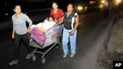 Una madre empuja una carretilla en la que viaja su hija al evacuar sus casas luego de la fuerte réplica el miércoles por la noche.