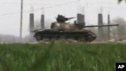 Gambar yang diambil dari video amatir ini menunjukkan tank militer di Deir el-Zour, Suriah (26/3). Diplomat Barat skeptis atas gencatan senjata di Suriah.Suriah meni