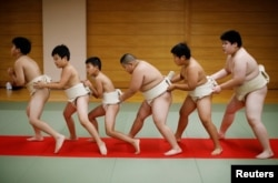 "Kyuta Kumagai, 10, warms up with other boys before training, at Komatsuryu sumo club in Tokyo, Japan, August 23, 2020. ""It is fun to beat people older than me,"" said Kyuta. (REUTERS/Kim Kyung-Hoon)"