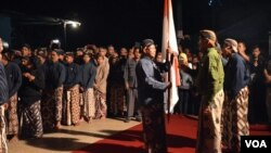 "GBPH Prabukusumo (kanan baju hijau) melepas peserta kirab ""Mubeng Beteng"" dengan menyerahkan panji-panji kepada wakil peserta, Kamis 15/10 dini hari (foto: VOA/Munarsih)."