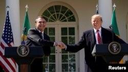 El presidente de EE.UU. Donald Trump y el visitante presidente de Brasil, Jair Bolsonaro, se dan la mano durante una conferencia de prensa conjunta en el Jardín de las Rosas de la Casa Blanca, el martes 19 de marzo de 2019.