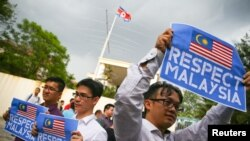 FILE - Members of the youth wing of the National Front, Malaysia's ruling coalition, hold placards during a protest at the North Korea embassy, following the murder of Kim Jong Nam, in Kuala Lumpur, Malaysia, Feb. 23, 2017.