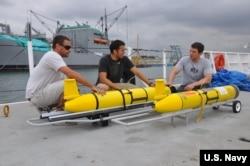 """工程技术人员为""""探路者""""号海洋测量船部署无人潜航器做准备。""""鲍迪奇""""号为同级海洋测量船。"""