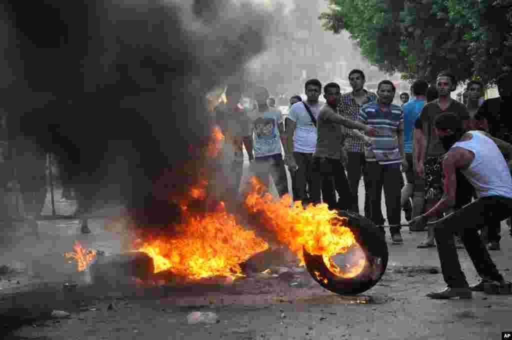 معترضین مصری در جریان زدوخورد با پلیس ضد شورش در مقابل سفارت امریکا در قاهره لاستیک های اتومبیل را آتش می زنند.