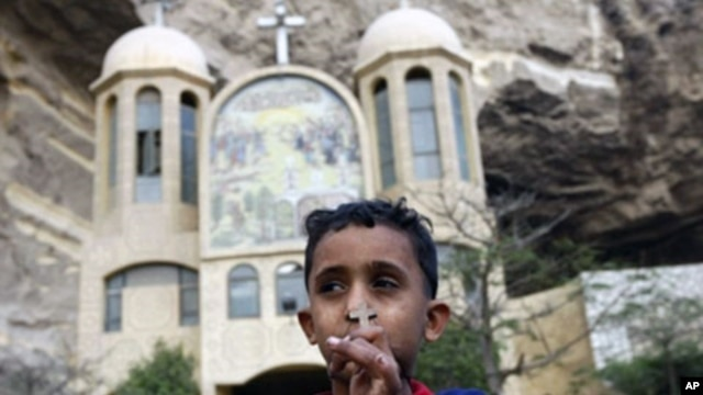 An Egyptian Christian boy holds a cross pendant outside a Coptic church in Cairo. Egyptian security forces began throwing up a cordon of steel as Coptic Christians prepared to mark Christmas after a New Year's Day church bombing killed 21 people in Alexan