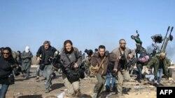 Các nhà báo và nhiếp ảnh gia chạy tìm nơi ẩn nấp một cuộc đánh bom do máy bay của chính phủ Libya thực hiện gần các nhà máy lọc dầu ở Ras Lanuf