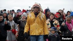 Chief Arvol Looking Horse, spiritual leader of the Sioux Nation, leads his people to peacefully pray near a law enforcement barricade just outside a Dakota Access pipeline construction site north of Cannon Ball, North Dakota, Oct. 29, 2016.