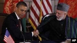 Tổng thống Hoa Kỳ Barack Obama (trái) và Tổng thống Afghanistan Hamid Karzai bắt tay trước khi ký một ký thỏa thuận đối tác chiến lược tại dinh tổng thống ở thủ đô Kabul, Afghanistan hôm 1/5/12