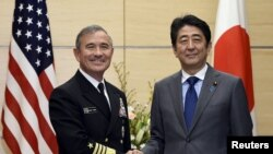 FILE - Japan's Prime Minister Shinzo Abe shakes hands with US Navy Admiral Harry B. Harris Jr., commander of the United States Pacific Command, before talks at Abe's official residence in Tokyo, Japan, Feb. 16, 2016.